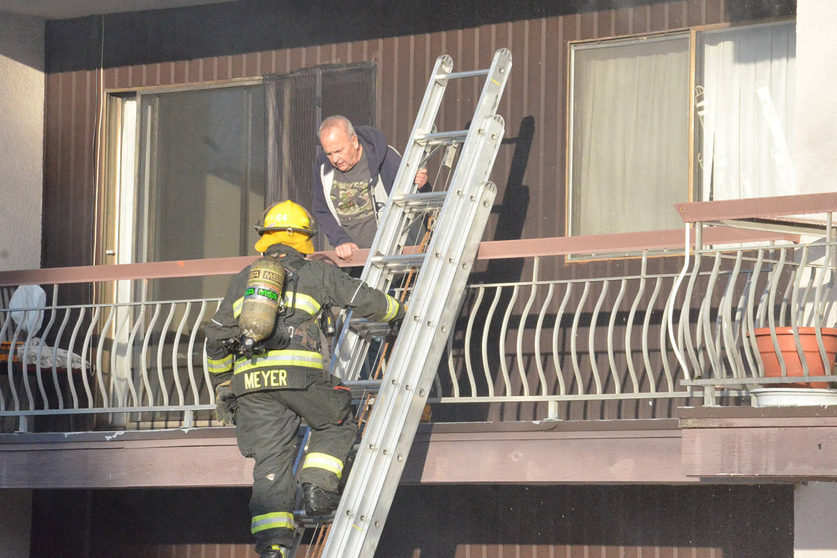 Firefighters climbed ladders to help a few tenants out of the apartment building. (Heather Colpitts/Langley Advance Times)