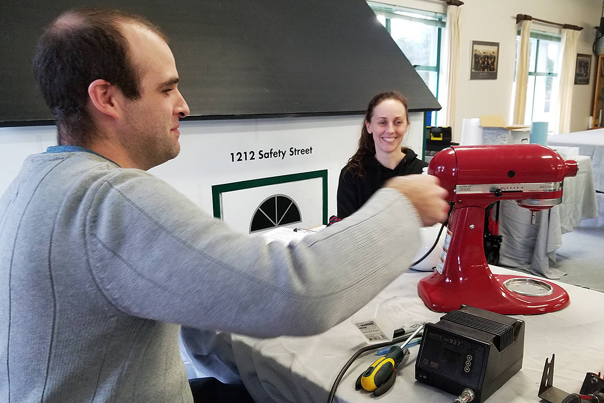 Electrician Bryce McLean managed to get the low speed working on Niki Berry's mixer at the first repair cafe in Langley on Saturday, Nov. 30th. (Dan Ferguson/Langley Advance Times)