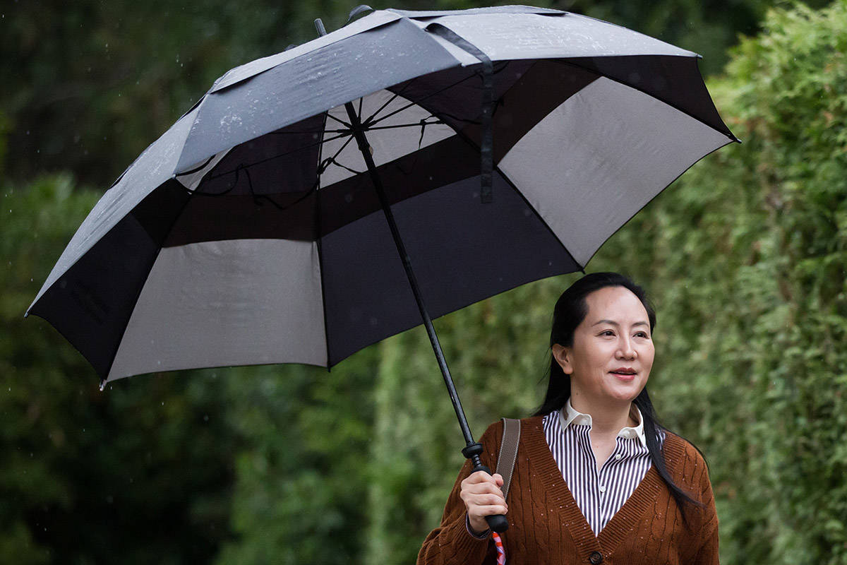 Huawei chief financial officer Meng Wanzhou, who is out on bail and remains under partial house arrest after she was detained last year at the behest of American authorities, carries an umbrella to shield herself from rain as she leaves her home to attend a court hearing, in Vancouver, Thursday, Oct. 3, 2019. THE CANADIAN PRESS/Darryl Dyck