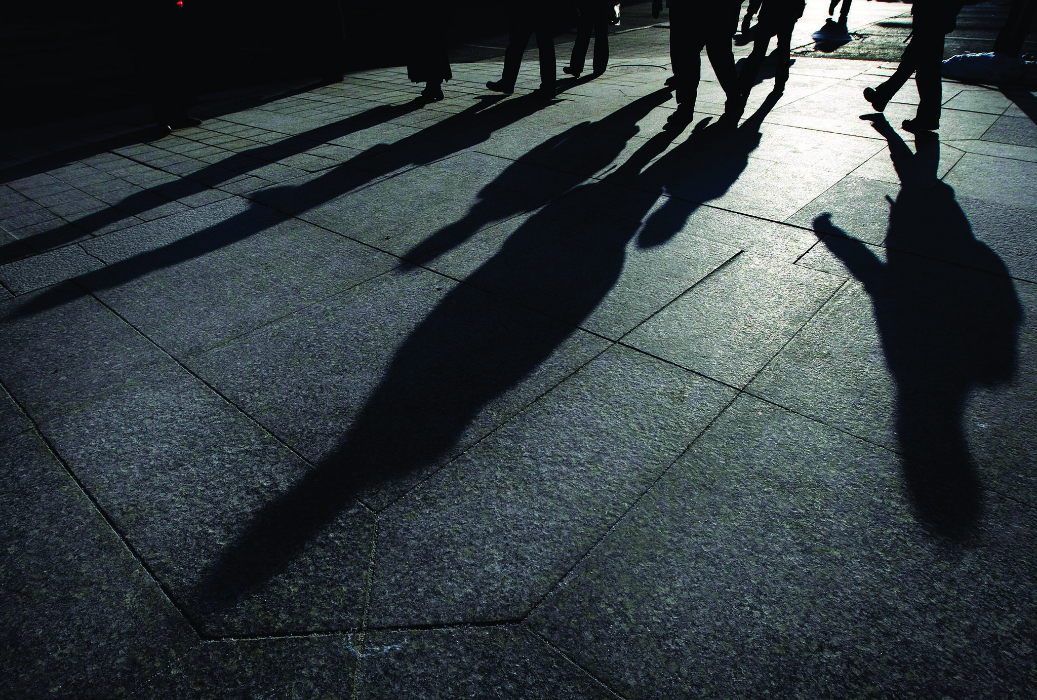 People cast their shadows on the sidewalks as they make their way home after work in downtown Toronto on Tuesday, Feb. 24, 2009. THE CANADIAN PRESS/Nathan Denette