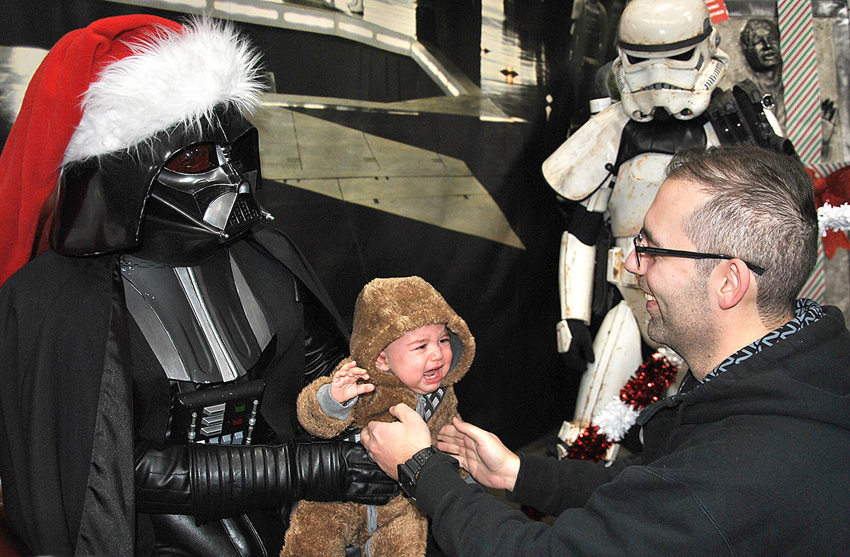 Despite adorning a Santa hat, the villianous Darth Vader wasn't loved by all who came to see him Sunday. He had young Lucy in tears. (Roxanne Hooper/Langley Advance Times)