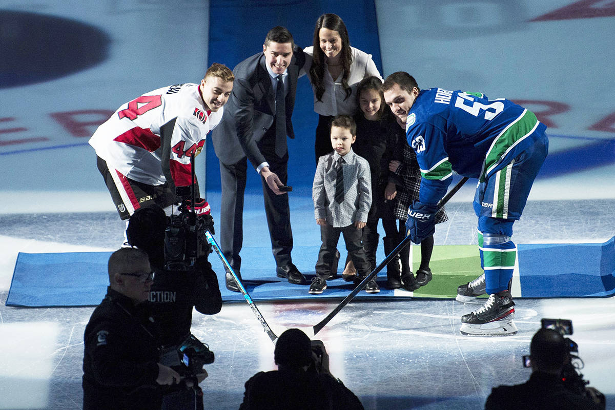 Former Vancouver Canucks player Alex Burrows takes part in a ceremonial puck drop with Vancouver Canucks centre Bo Horvat (53) and Ottawa Senators centre Jean-Gabriel Pageau (44) prior to the first period in Vancouver, Tuesday, Dec. 3, 2019. Burrows was inducted into the Vancouver Canucks Ring of Honour. THE CANADIAN PRESS/Jonathan Hayward