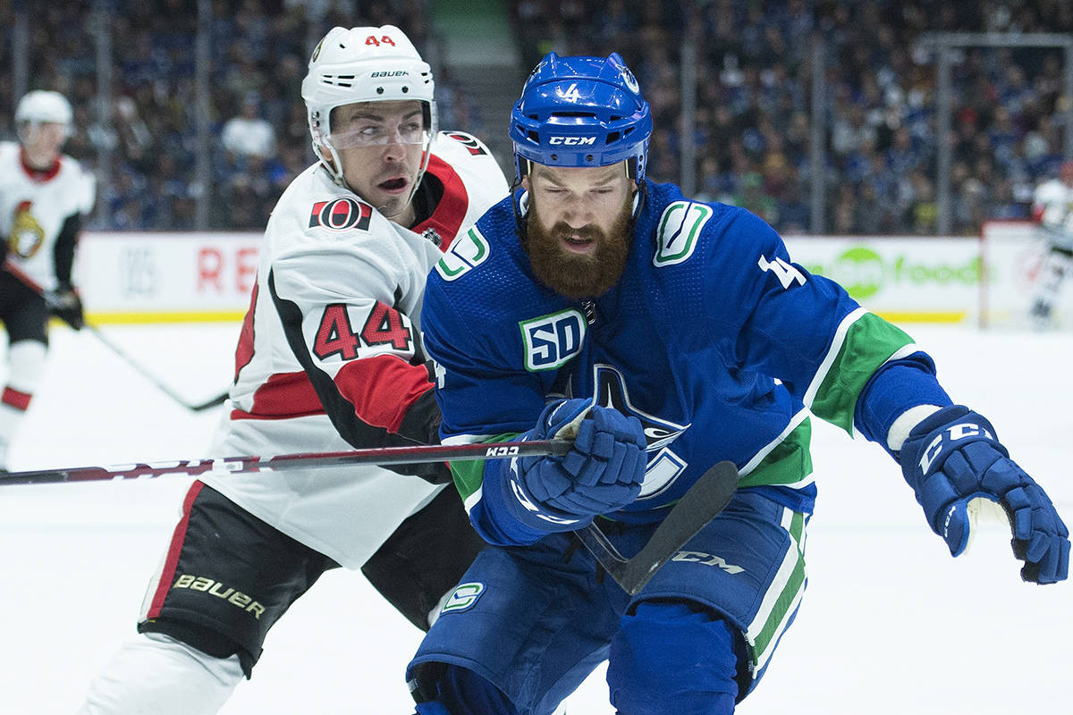 Ottawa Senators centre Jean-Gabriel Pageau (44) fights for control of the puck with Vancouver Canucks defenceman Jordie Benn (4) during first period NHL action in Vancouver, Tuesday, Dec. 3, 2019. THE CANADIAN PRESS/Jonathan Hayward