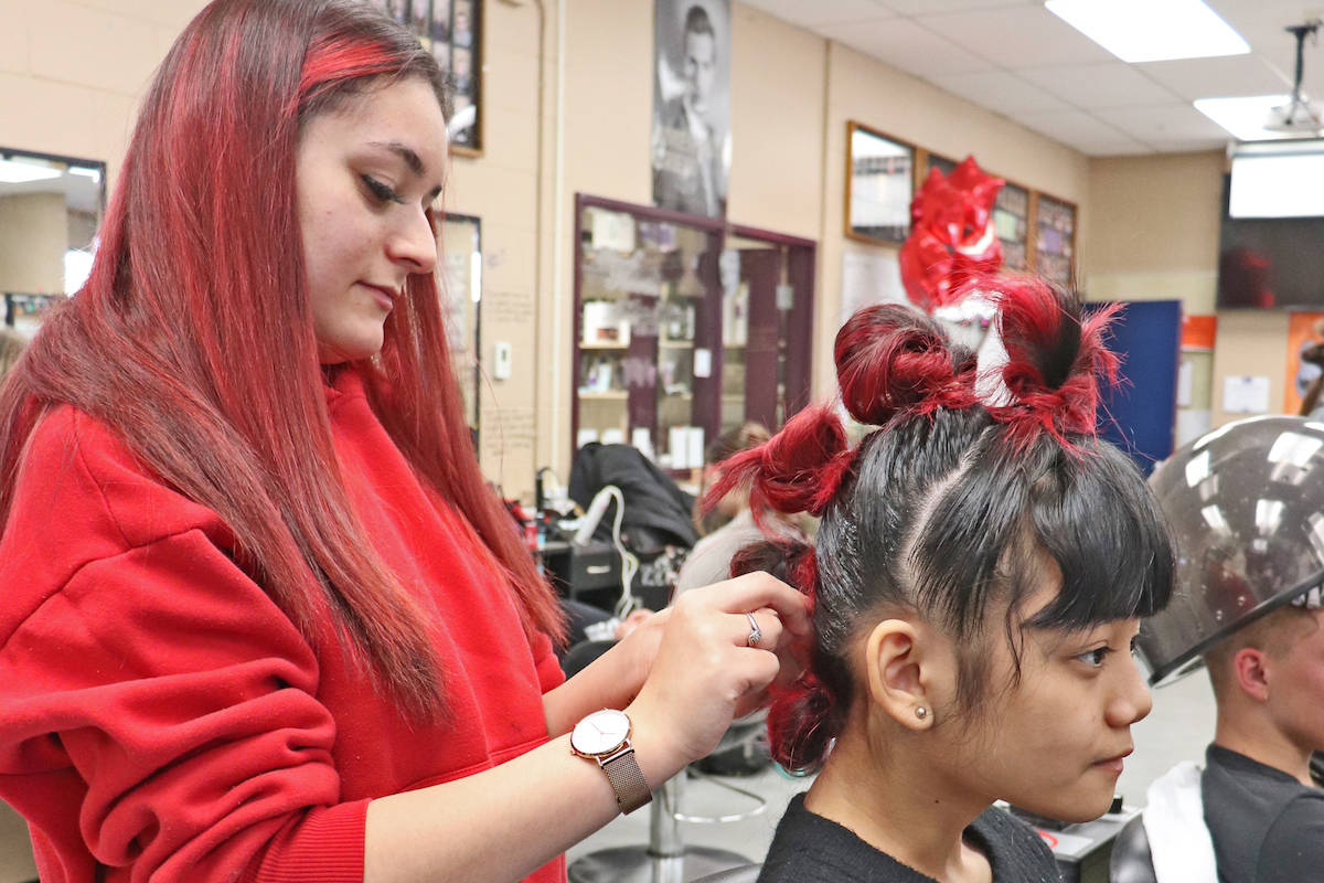 Student stylist Alexa Adams prepped her model's hair; dyed red and styled in cascading buns for the showcase. (Sarah Grochowski photo)