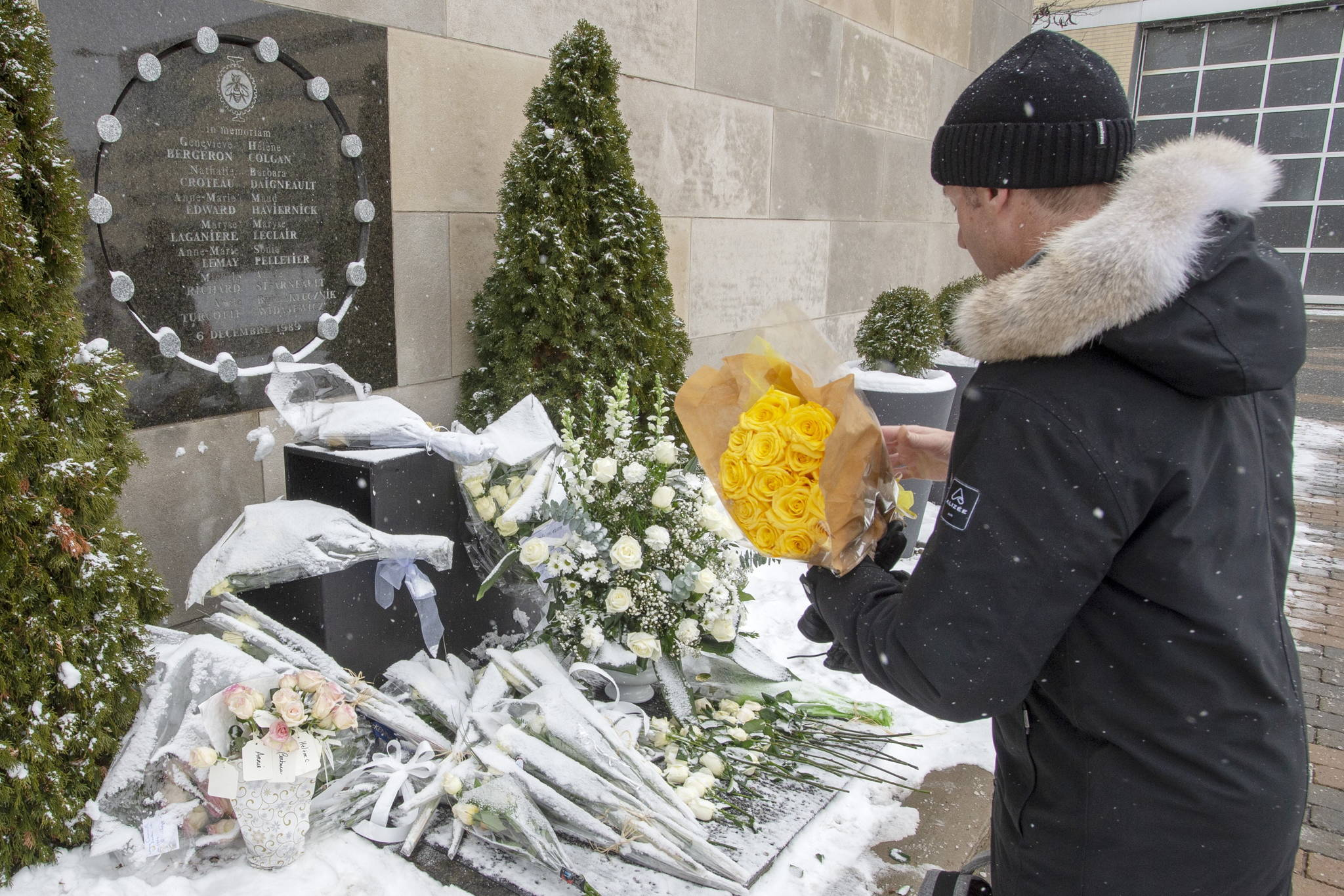 Former student Richard Gregoire places fourteen roses at the school's memorial to mark the 30th anniversary of the 1989 Ecole Polytechnique attack where a lone gunman killed 14 female students Friday, December 6, 2019 in Montreal. THE CANADIAN PRESS/Ryan Remiorz