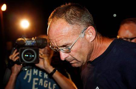 FILE - Douglas Garland is escorted into a Calgary police station in connection with the disappearance of Nathan O'Brien and his grandparents in Calgary, Alta., Monday, July 14, 2014. (Jeff McIntosh / THE CANADIAN PRESS)