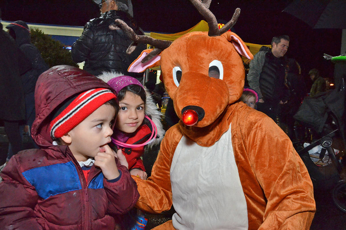 Mashal, two, and six-year-old Alishba Shehzad met Rudolph the Red Nose Reindeer at Brookswood Night of Lights on Friday evening. (Heather Colpitts/Langley Advance Times)