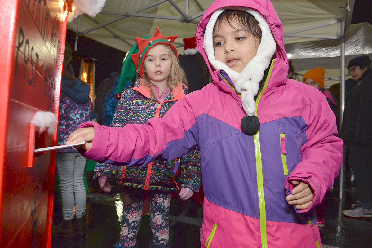 Sarina Rodrigez, four, mailed her letter to Santa at Brookswood Night of Lights. Helping at the booth was special elf Zoey. (Heather Colpitts/Langley Advance Times)