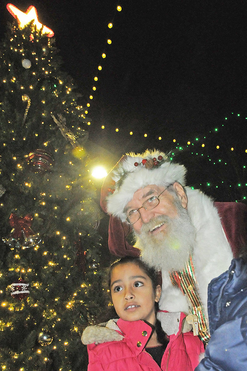 Six-year-old Pihu Kapoor from Willoughby had a close encounter with the jolly old elf at the Christmas tree lighting at the end of the Magic of Christmas parade in Langley City Saturday night (Dec. 7). (Dan Ferguson/Langley Advance Tines)