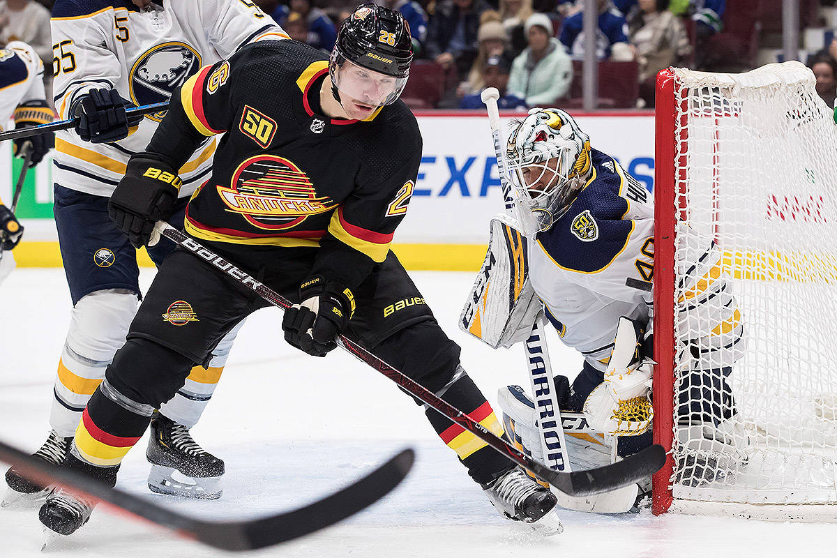Vancouver Canucks' Antoine Roussel, left, of France, watches the puck as it bounces off the post beside Buffalo Sabres goalie Carter Hutton during the second period of an NHL hockey game in Vancouver, on Saturday December 7, 2019. THE CANADIAN PRESS/Darryl Dyck