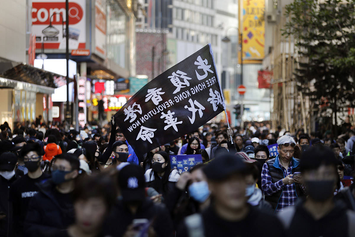 Pro-democracy protesters march on a street in Hong Kong, Sunday, Dec. 8, 2019. Marchers are again expected to fill Hong Kong streets Sunday in a rally that will test the enduring appeal of an anti-government movement marking a half year of demonstrations. (AP Photo/Vincent Thian)