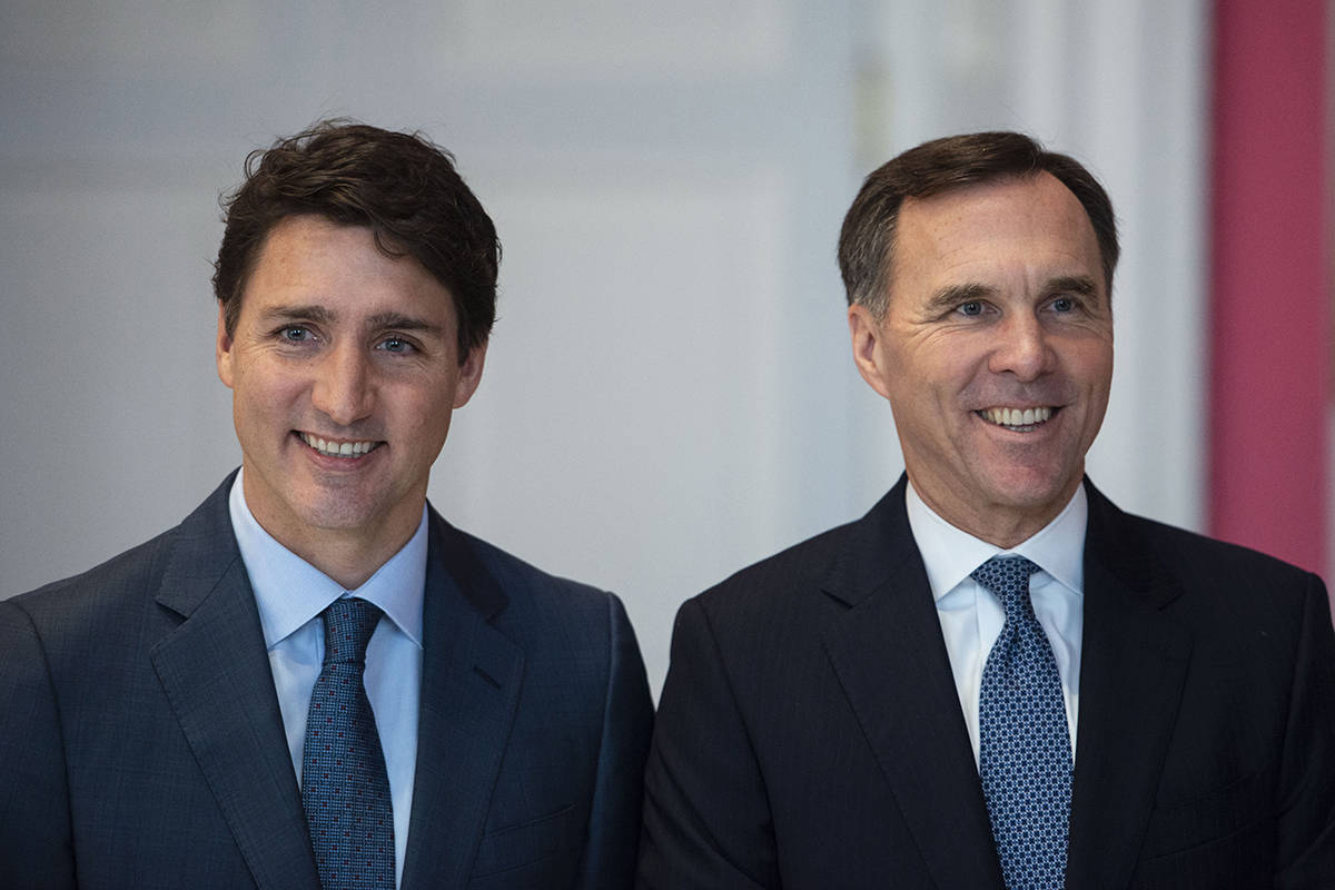 """Prime Minister Justin Trudeau stands with Bill Morneau as he remains Minister of Finance during the swearing in of the new cabinet at Rideau Hall in Ottawa on Wednesday, Nov. 20, 2019. The Conservatives are calling on Finance Minister Bill Morneau to deliver an """"urgent"""" fall economic update, including a plan to get back to balance. THE CANADIAN PRESS/Sean Kilpatrick"""