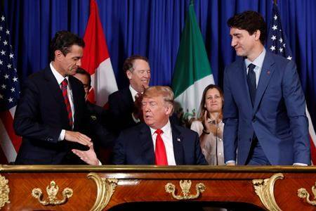 President Donald Trump shakes hands with Mexico President Enrique Pena Neto, left, as Canada's Prime Minister Justin Trudeau, right, looks on after participating in the USMCA signing ceremony, Friday, Nov. 30, 2018 in Buenos Aires, Argentina. A deal on amending the new North American free trade agreement appears close following a busy weekend, with hopes Canada, Mexico and the United States will approve a rewritten deal in the next 24 hours. (THE CANADIAN PRESS/AP-Pablo Martinez Monsivais)