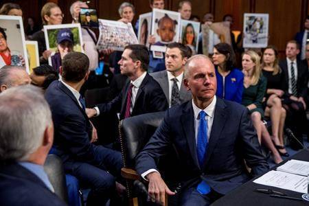 FILE - In this Oct. 29, 2019 file photo, Boeing Company President and Chief Executive Officer Dennis Muilenburg, right foreground, watches as family members hold up photographs of those killed in the Ethiopian Airlines Flight 302 and Lion Air Flight 610 crashes during a Senate Committee on Commerce, Science, and Transportation hearing on Capitol Hill. (AP Photo/Andrew Harnik, File)