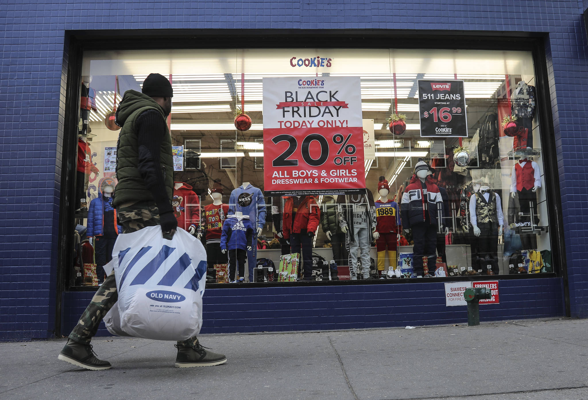 FILE - In this Nov. 29, 2019, file photo people walk by a Black Friday promotional at Cookie's department store in the Brooklyn Borough of New York. Shopping at sales and using coupons may not be saving you as much money as you think. Knowing the pitfalls and having a plan can help keep your holiday shopping from coming back to bite you in January. (AP Photo/Bebeto Matthews, File)