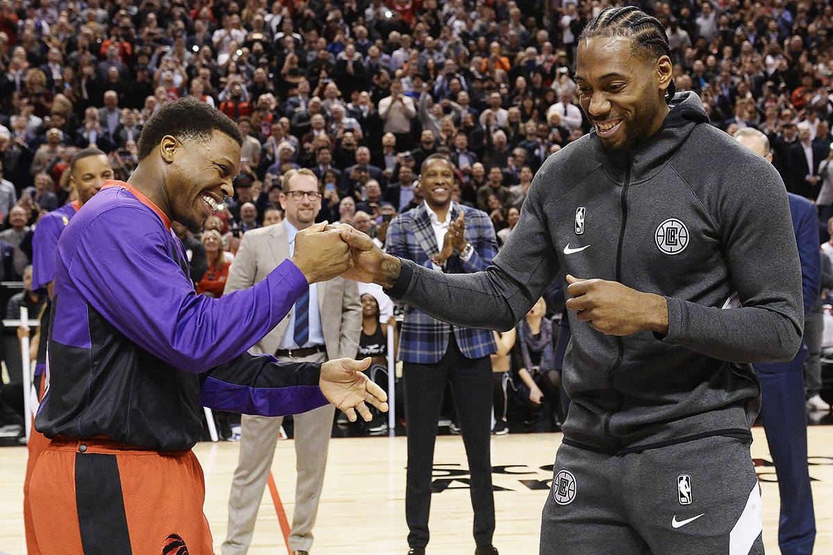 Former Toronto Raptors and now LA Clippers forward Kawhi Leonard, right, receives his 2019 NBA championship ring from Raptors' Kyle Lowry prior to NBA basketball action in Toronto on Wednesday, Dec. 11, 2019. THE CANADIAN PRESS/Nathan Denette