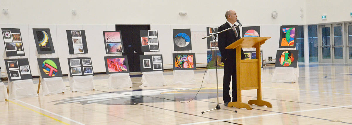 In front of a display of student art, Langley School District superintendent Gord Stewart spoke at the grand opening ceremony for R.E. Mountain Secondary on Dec. 12, (Heather Colpitts/Langley Advance Times)