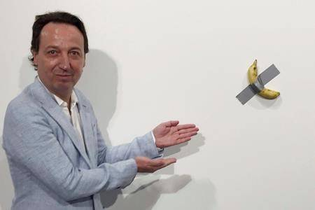 """In this Dec. 4, 2019 photo, gallery owner Emmanuel Perrotin poses next to Italian artist Maurizio Cattlelan's """"Comedian"""" at the Art Basel exhibition in Miami Beach, Fla. The work sold for $120,000. (Siobhan Morrissey via AP)"""
