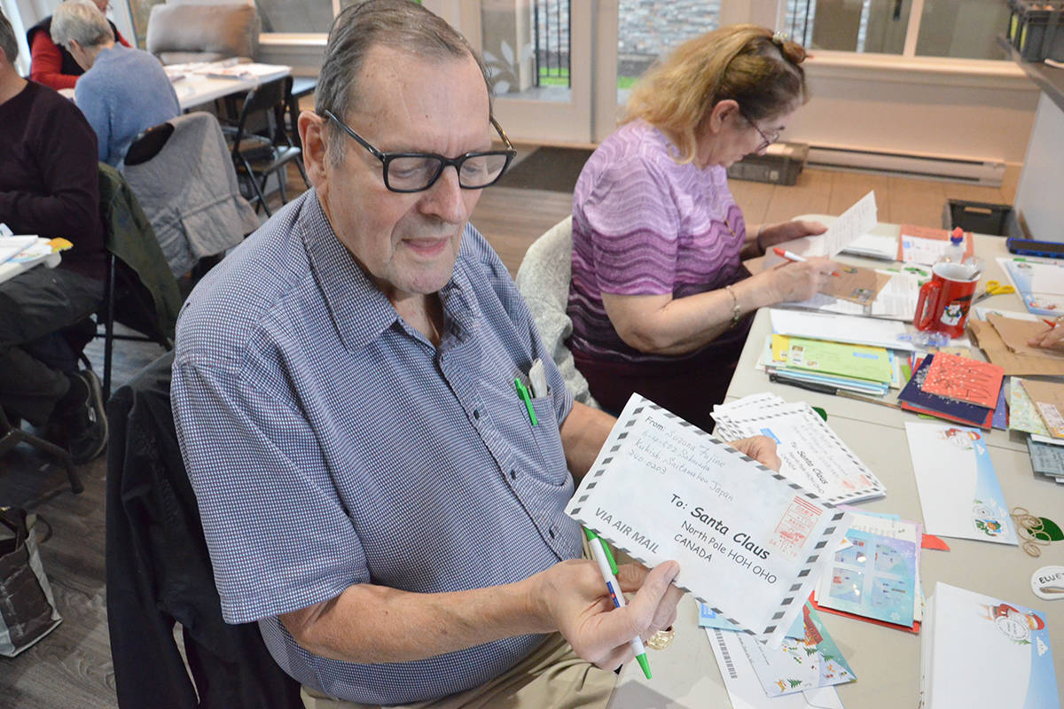 Bruce Mavis, a retired postal worker and longtime postal elf, shows one of the letters that came this year from Japan. (Heather Colpitts/Langley Advance Times)