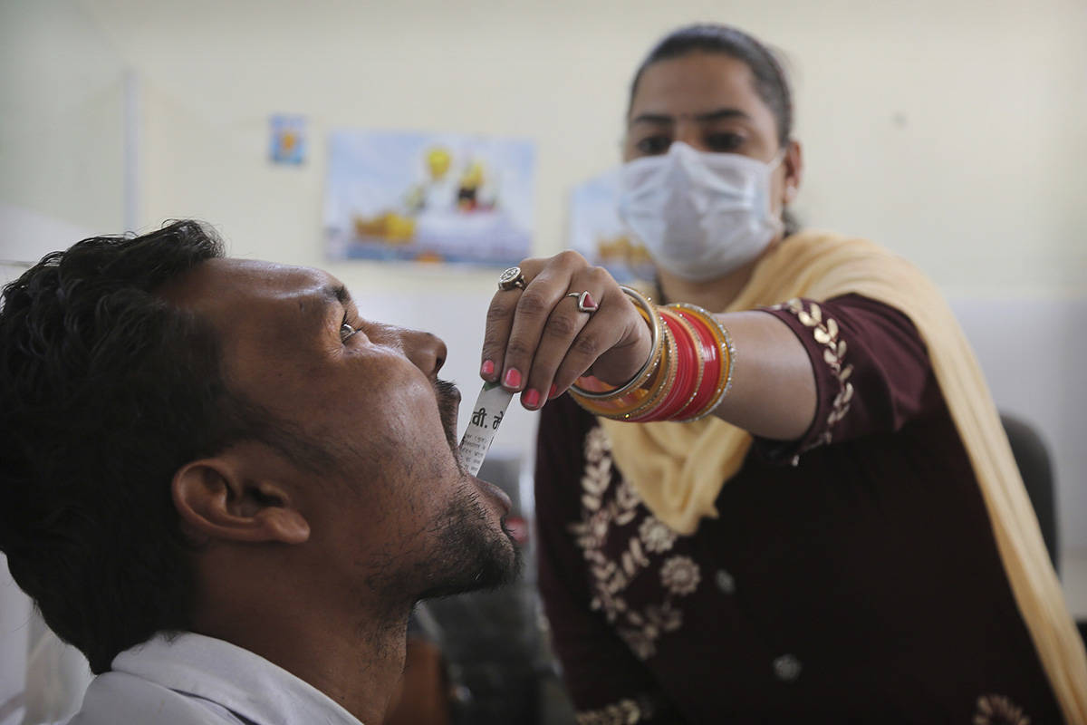 """In this Thursday, Oct. 31, 2019, photo, a medic administers medicine to a recovering drug addict at a de-addiction center in Kapurthala, in the northern Indian state of Punjab. Researchers estimate about 4 million Indians use heroin or other opioids, and a quarter of them live in the Punjab, India's agricultural heartland bordering Pakistan. These pills, the world had been told, were safer than the OxyContins, the Vicodins, the fentanyls that had wreaked so much devastation. But now they are the root of what the United Nations named """"the other opioid crisis,"""" an epidemic featured in fewer headlines than the American one, as it rages through the most vulnerable places on the planet. (AP Photo/Channi Anand)"""