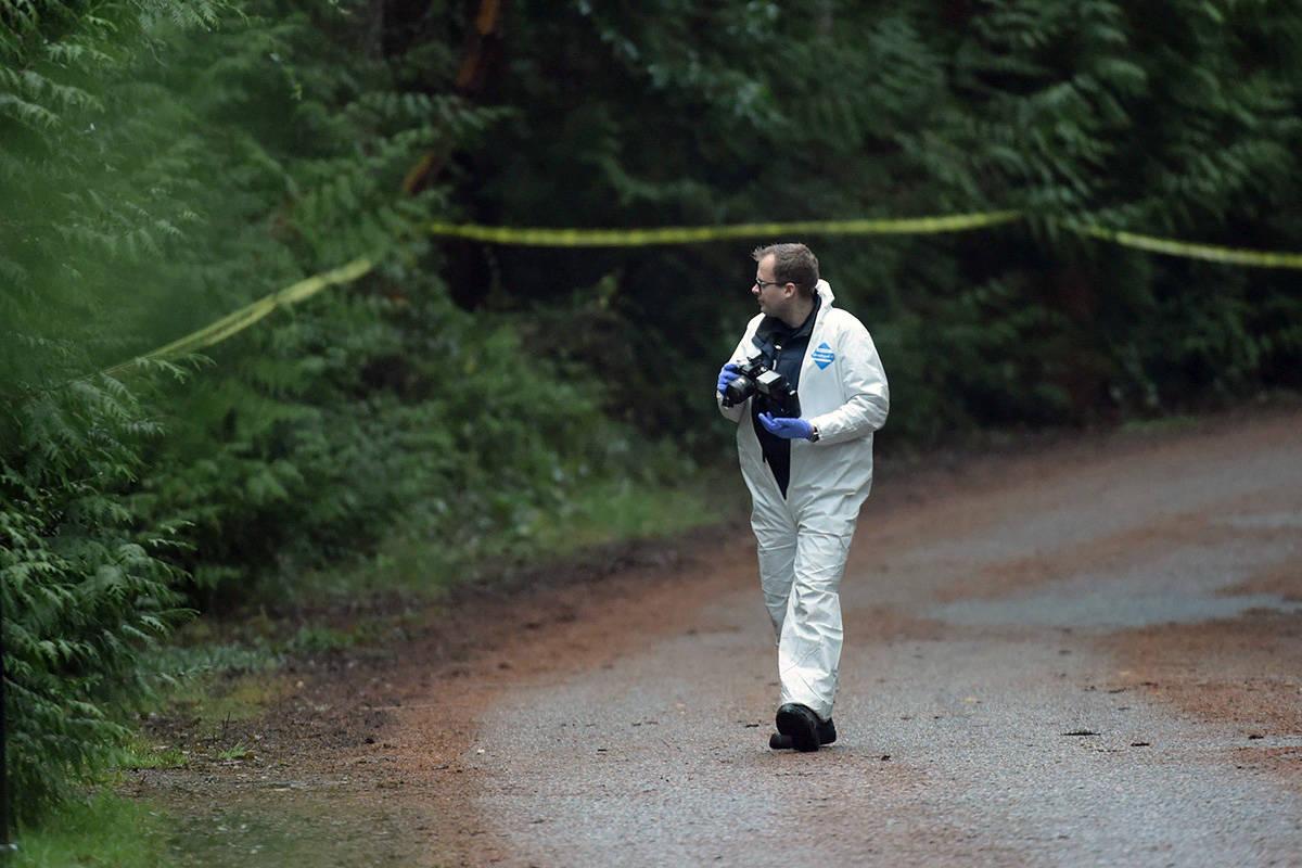 An investigator takes photos near the scene of a small plane crash on Gabriola Island, B.C., Wednesday, Dec. 11, 2019. THE CANADIAN PRESS/Jonathan Hayward