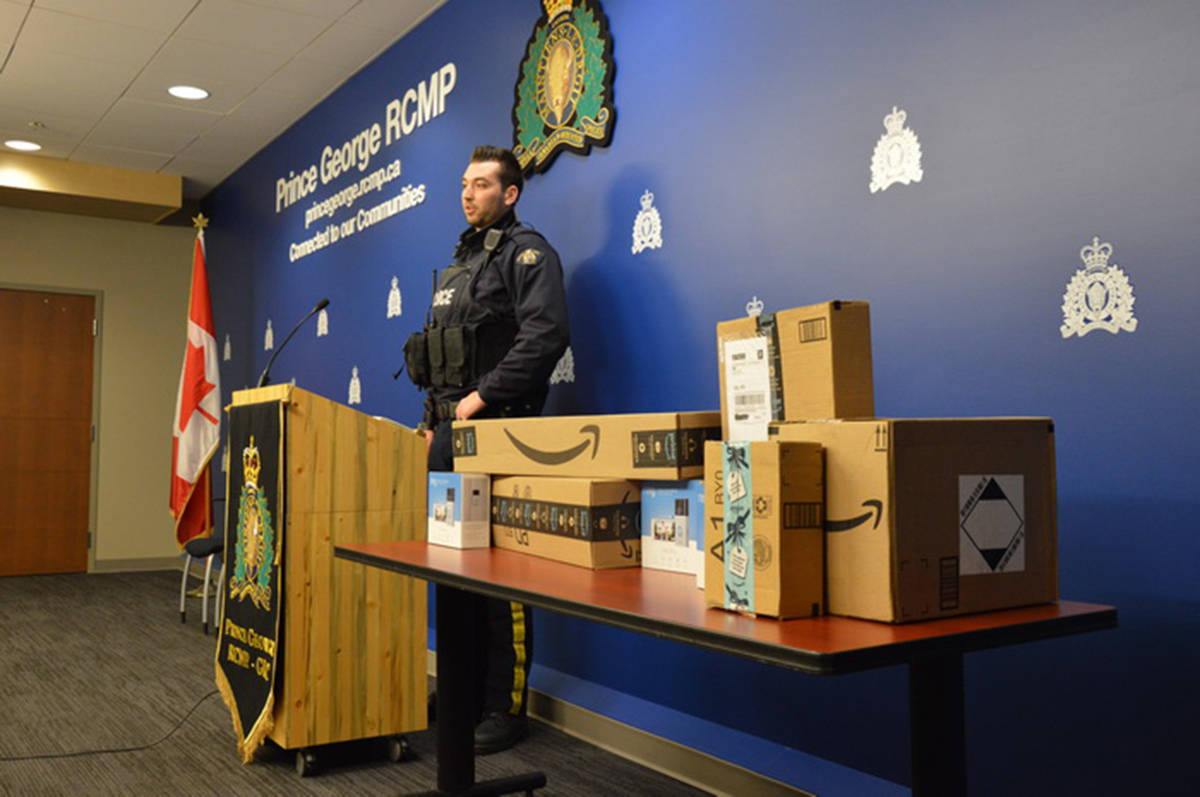 Const. Brent Benbow standing next to Amazon packaging as he speaks to media in Prince George on Dec. 11, 2019. (Prince George RCMP handout)