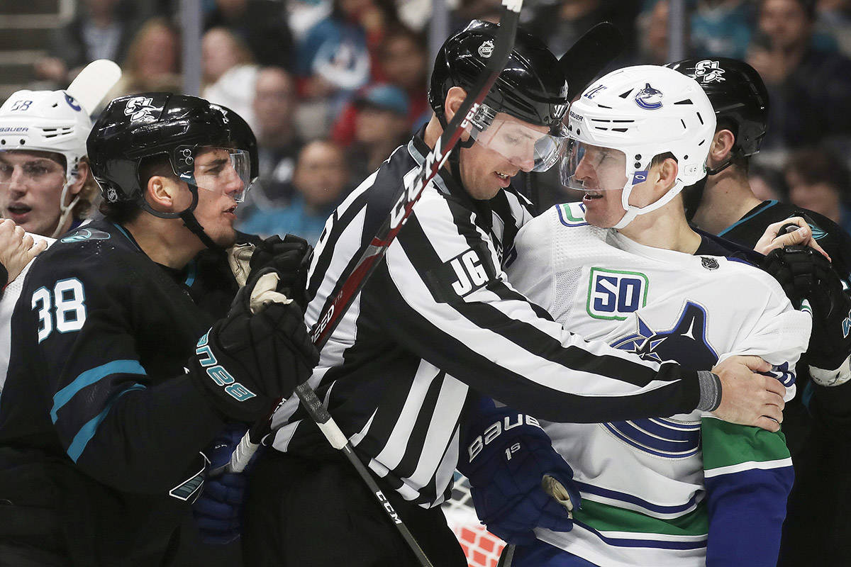 San Jose Sharks defenceman Mario Ferraro, left, goes after Vancouver Canucks left wing Antoine Roussel, right, during the second period of an NHL hockey game in San Jose, Calif., Saturday, Dec. 14, 2019. (AP Photo/Jeff Chiu)