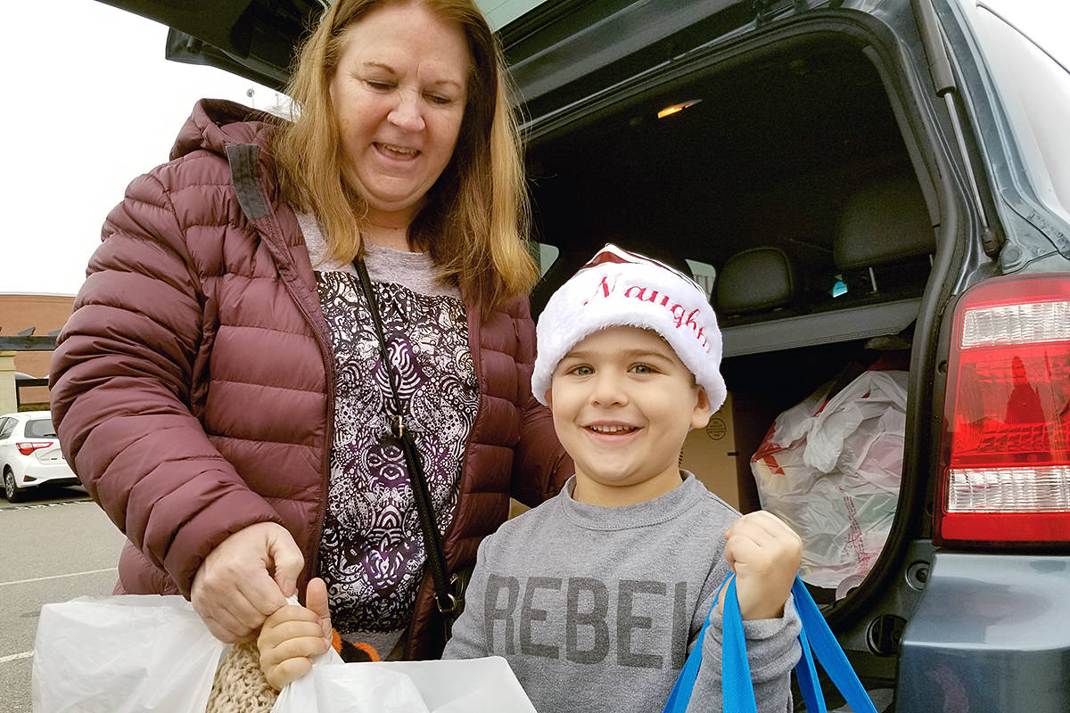 Wendi Bordelay and grandson Lennox Zulyniak brought contributions from Clayton Heights to donate to the 'fill the ambulance' donation drive by Kimz Angels at the Murrayville IGA on Saturday, Dec. 14. (Dan Ferguson/Langley Advance Times)