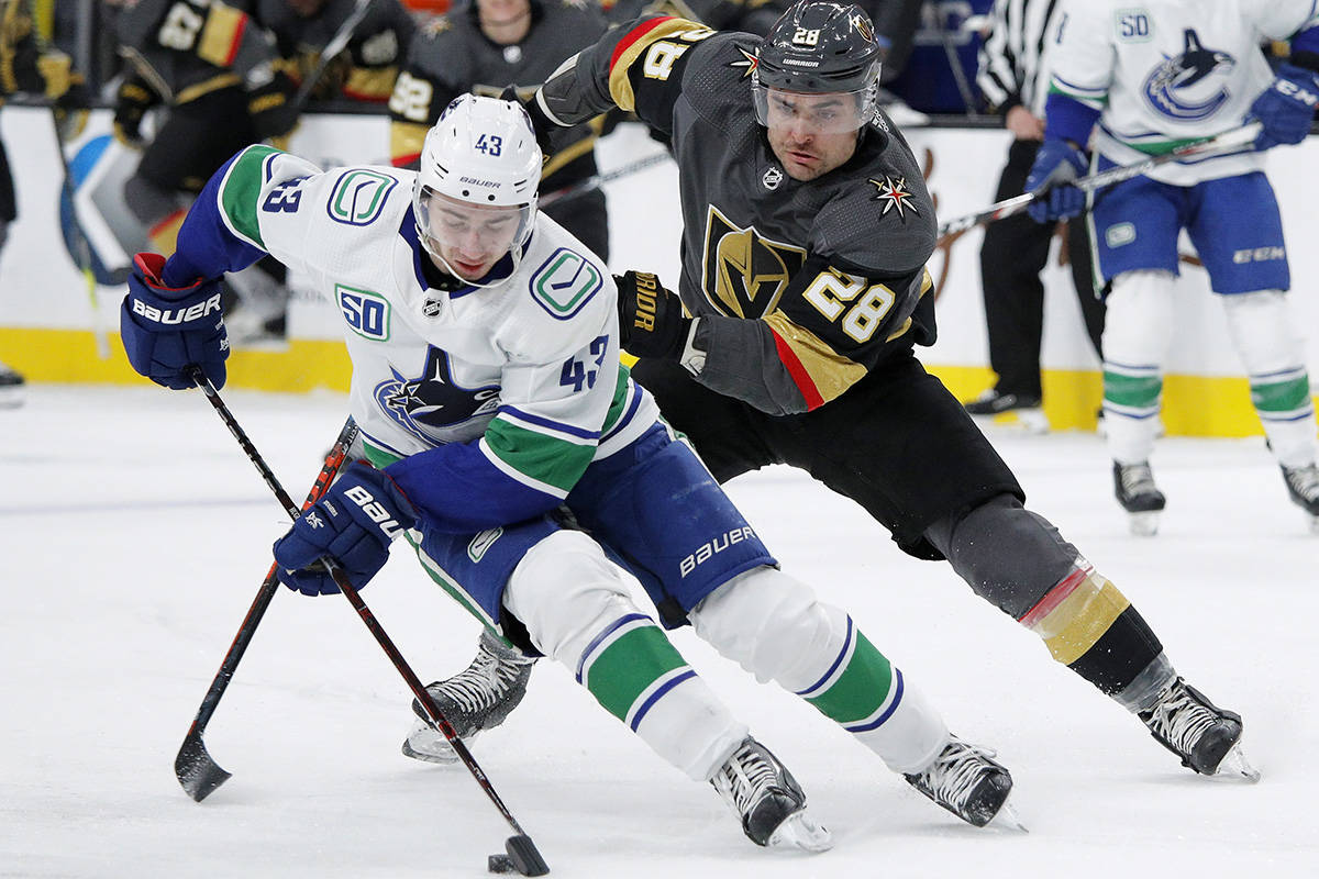 Vancouver Canucks defenceman Quinn Hughes (43) skates around Vegas Golden Knights left wing William Carrier (28) during the second period of an NHL game on Sunday, Dec. 15, 2019, in Las Vegas. (AP Photo/John Locher)