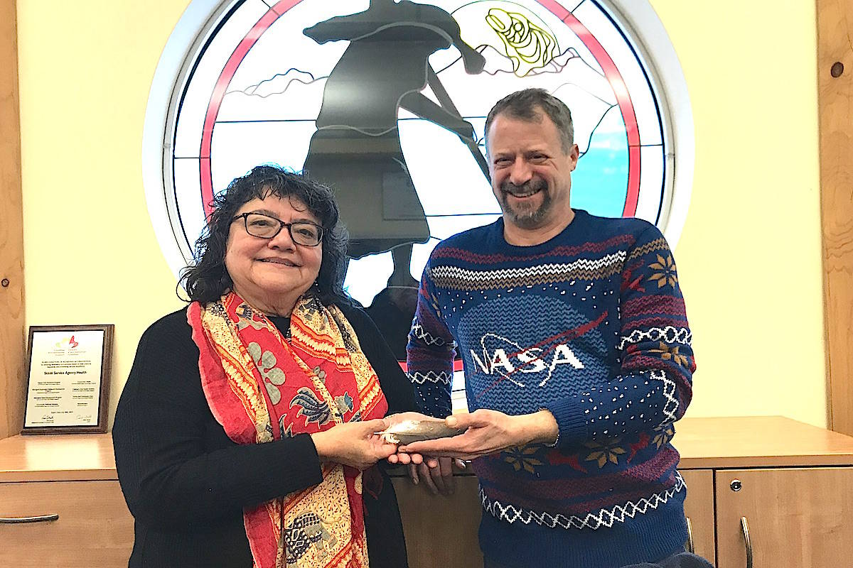 Sto:lo Nation Health director Kelowa Edel and Michael Suedfeld of Sto:lo Service Agency gingerly holding the first eagle feather ever to make it aboard the International Space Station. (Jennifer Feinberg/ The Progress)