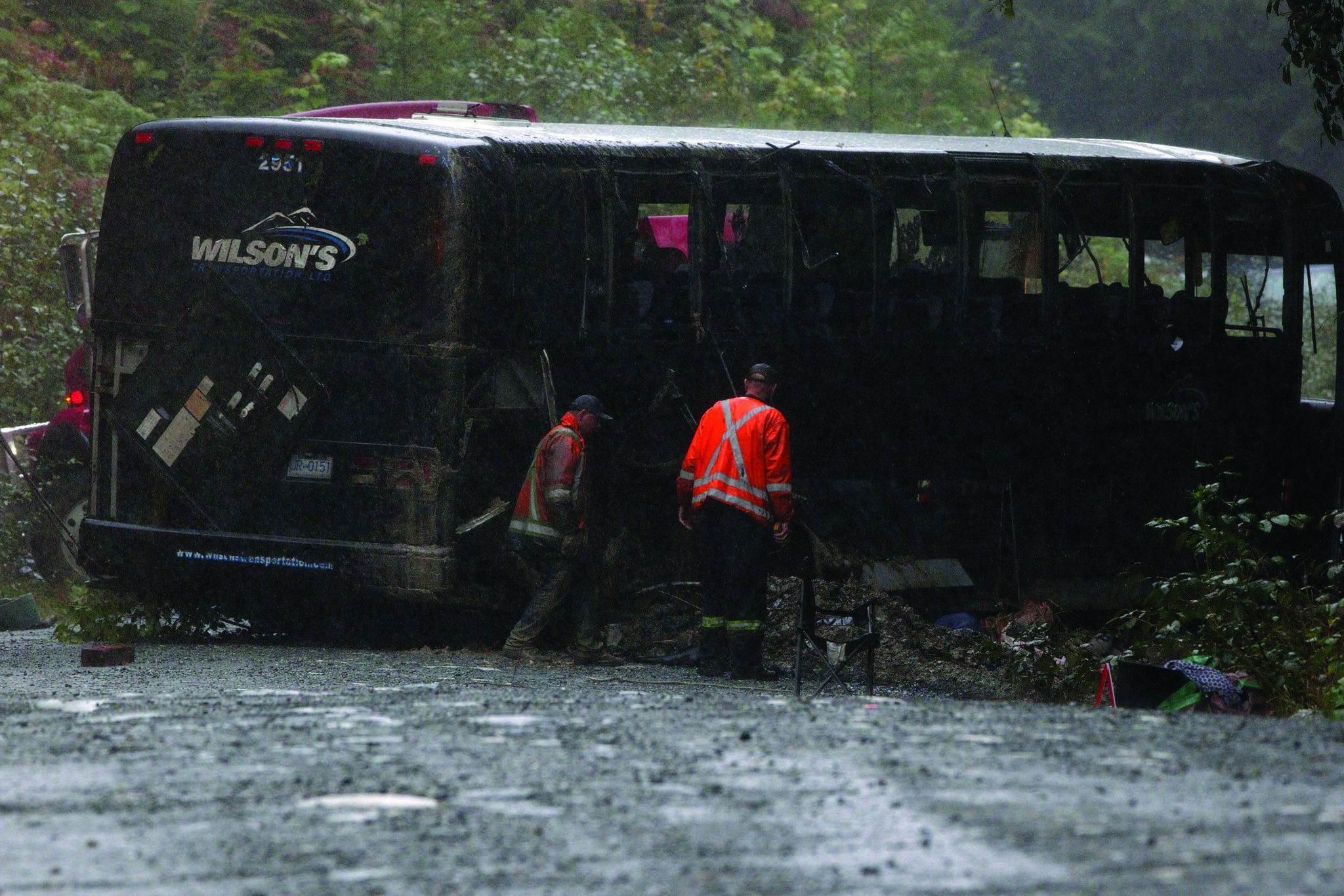 Search and rescue crews and RCMP help a tow-truck crew to remove a bus from the ditch of a logging road near Bamfield, B.C., on Saturday, September 14, 2019. Two University of Victoria students died and more than a dozen other people were injured after a bus on its way to a marine research centre rolled over on a narrow gravel road on Vancouver Island on Friday. The incident happened between the communities of Port Alberni and Bamfield, said the Joint Rescue Co-ordination Centre in Victoria, which received a call for assistance at around 10 p.m. THE CANADIAN PRESS/Chad Hipolito