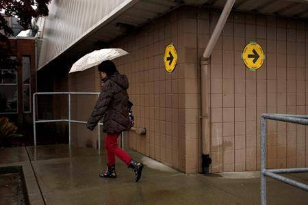 A woman walks by voting signage in Colwood, B.C., Monday, Oct. 21, 2019. THE CANADIAN PRESS/Chad Hipolito