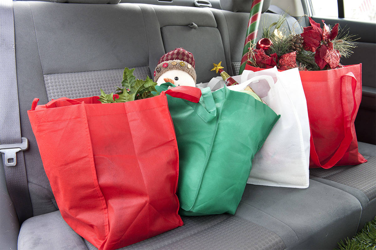 The back seat of a car with four bags of Christmas gifts and decor. (123rf.com)