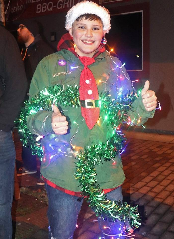 Twelve-year-old Taylor Berget marched in the parade as part of the legion Scouts crew, dressed in green tinsel, a Santa hat, and string lights. (Sarah Grochowski photo)
