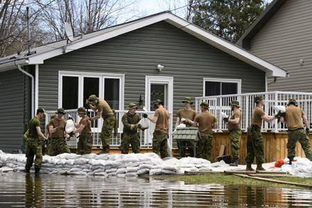 Soldiers work to hold back floodwaters on the Ottawa River in Cumberland. Ontario on Tuesday, April 30, 2019. THE CANADIAN PRESS/Sean Kilpatrick
