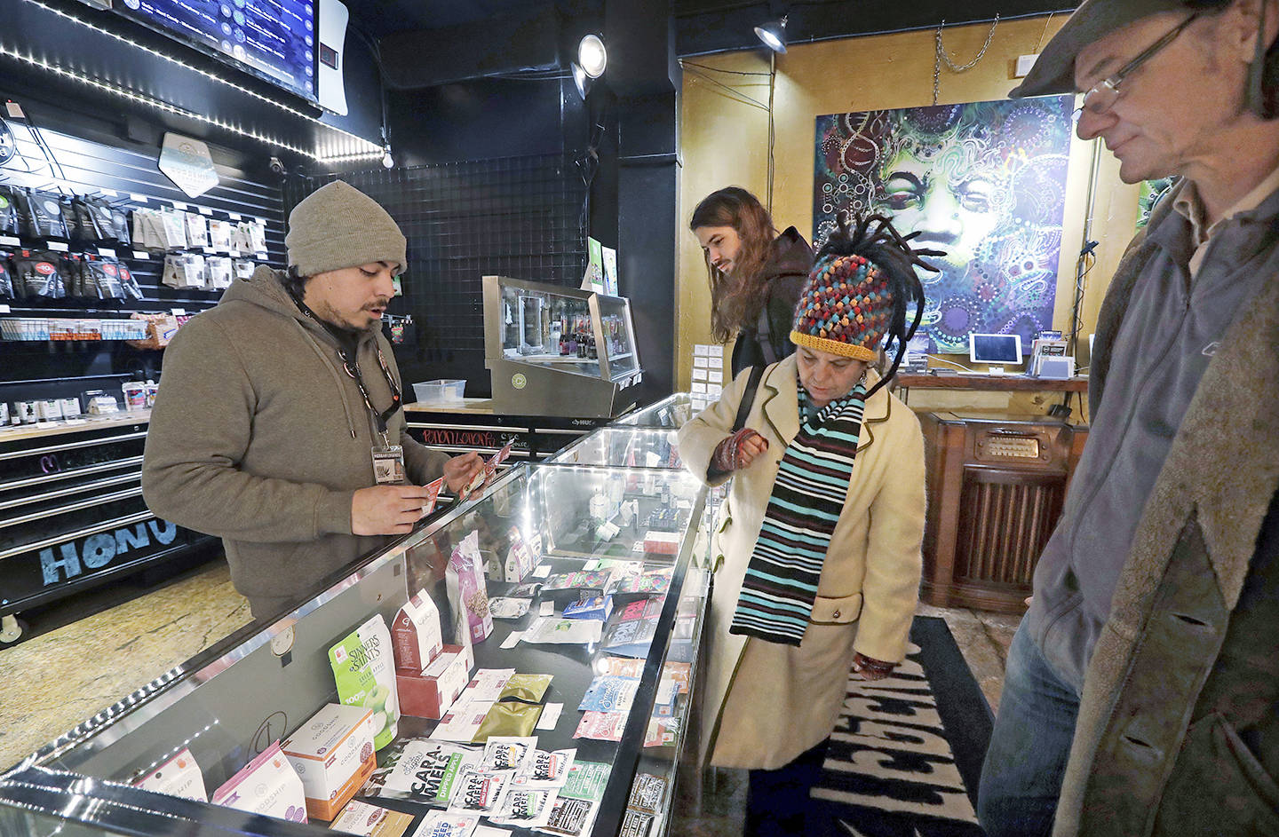 Cannabis consultant assists customers shopping for edible marijuana products in the Herban Legends shop in Seattle, Jan. 4, 2018. Edibles, extracts, vapourizers and beverages are now legal in Canada. (AP Photo/Elaine Thompson)