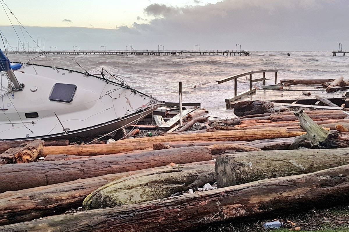 A shattered sailboat and remnants of the pier rest near the white rock, backdropped by the broken structure. (Christy Fox photo)