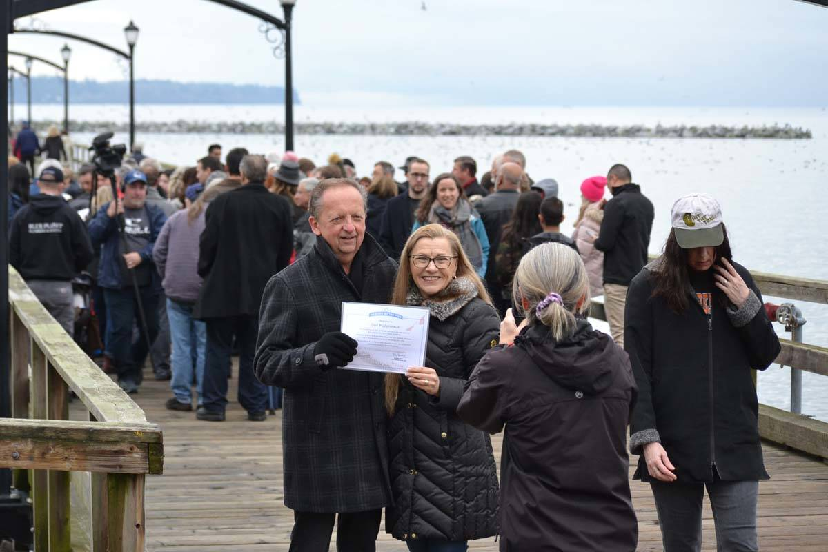 "Leo and Gail Molyneaux have their photograph taken with a Friends of the Pier certificate while a group (behind) wait to pick up their document. The certificate reads ""In recognition of your generous purchase of a new plank to help build the iconic White Rock Pier.' (Aaron Hinks file photo)"