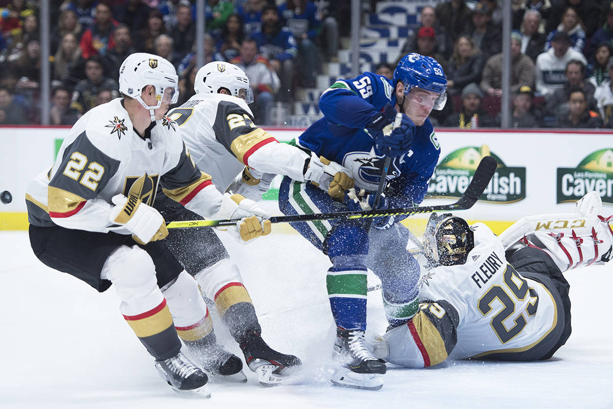 Vegas Golden Knights defenceman Nick Holden (22) and Shea Theodore (27) stop Vancouver Canucks centre Bo Horvat (53) from getting a shot past Vegas Golden Knights goaltender Marc-Andre Fleury (29) during second period NHL action in Vancouver, Thursday, Dec. 19, 2019. THE CANADIAN PRESS/Jonathan Hayward