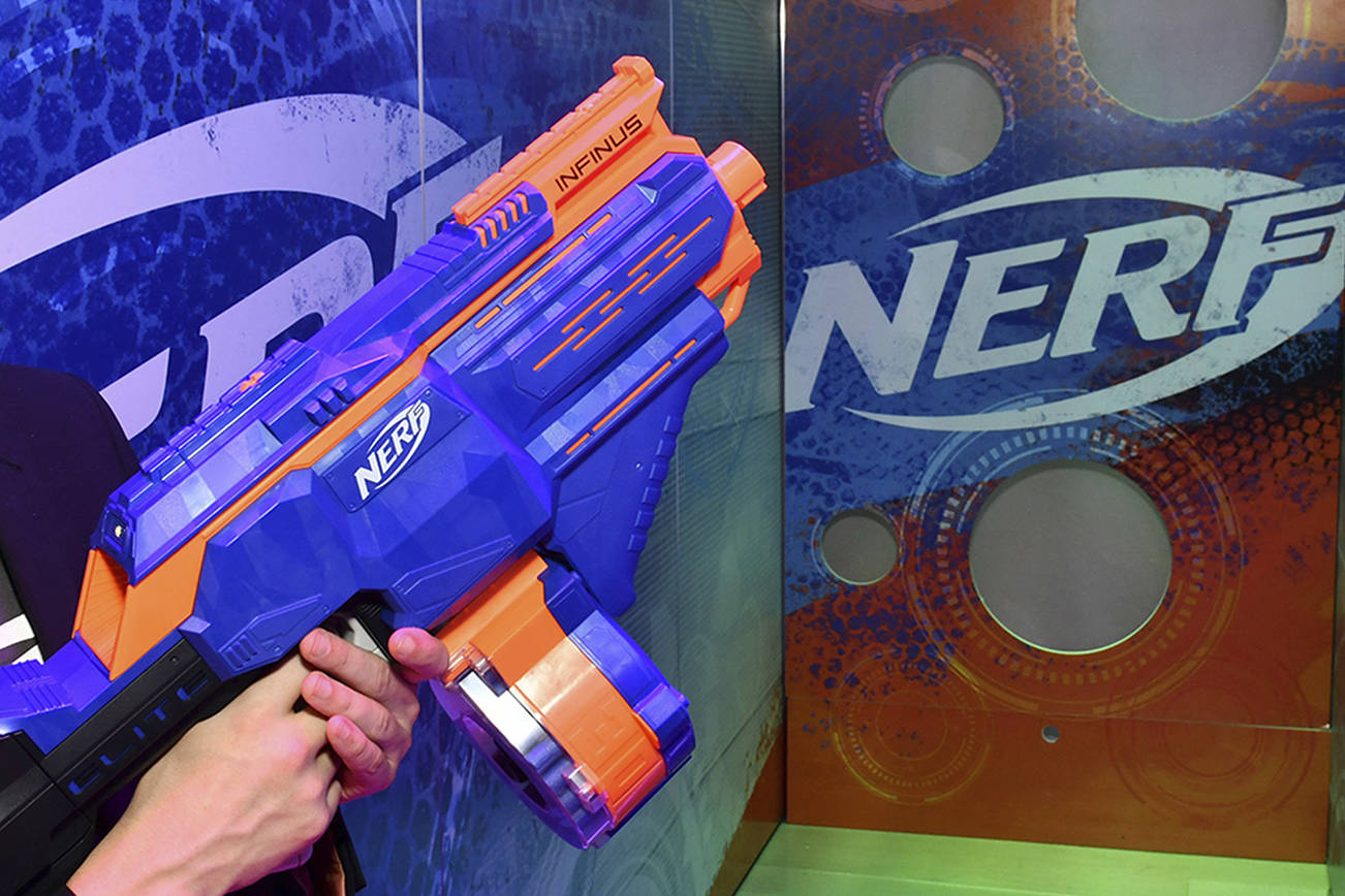"""A demonstrator at the Hasbro, Inc. showroom fires the NERF N-STRIKE ELITE INFINUS blaster at the American International Toy Fair on Feb. 16, 2018 in New York. A similar Nerf gun made the World Against Toys Causing Harm's 2018 list for """"10 worst toys."""" (Charles Sykes/Invision for Hasbro, Inc./AP Images)"""