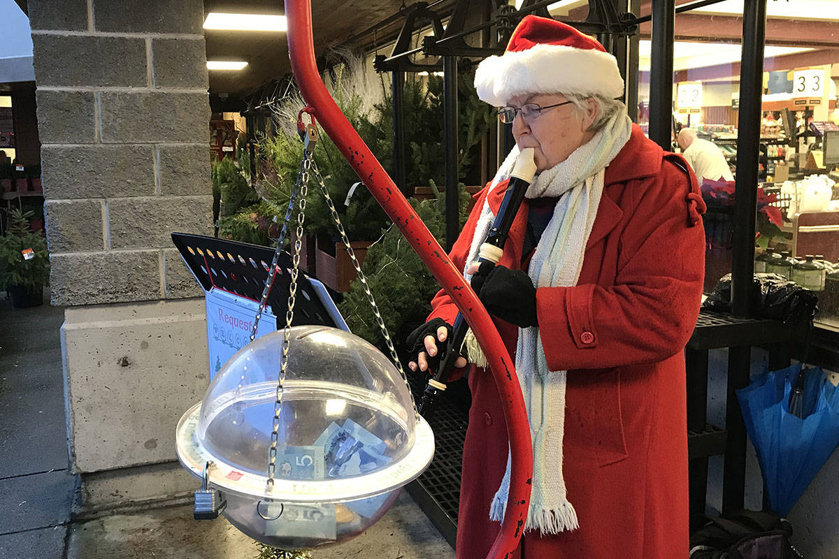 Salvation Army kettle volunteer Gillian Shearwater plays Christmas carols on her tenor recorder in front of Quality Foods on Dec. 11, 2019. This is Shearwater's 10th year volunteering for the annual kettle campaign. (SUSAN QUINN/Alberni Valley News)