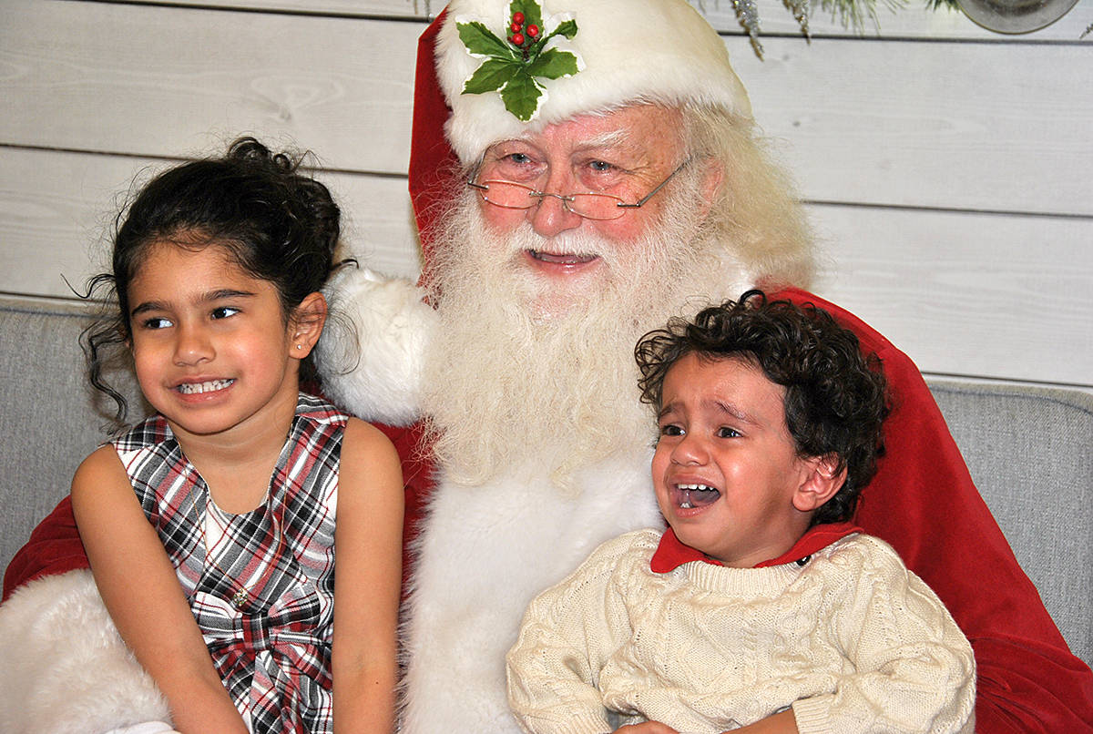 Twenty-month-old Nolan Sidhu, of Willoughby, wasn't as thrilled as some to sit on Santa's lap. (Roxanne Hooper/Langley Advance Times)