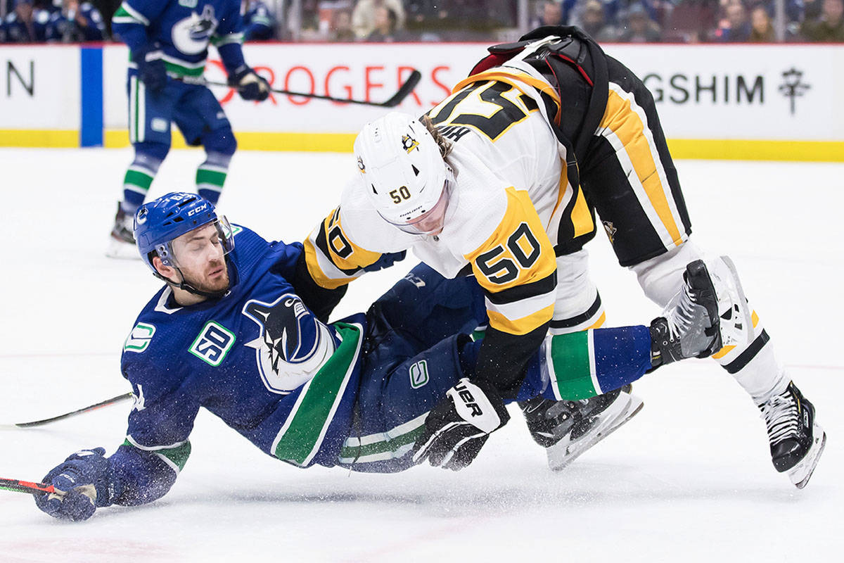 Pittsburgh Penguins' Juuso Riikola, right, of Finland, checks Vancouver Canucks' Tyler Motte during second period NHL hockey action in Vancouver, Saturday, Dec. 21, 2019. THE CANADIAN PRESS/Darryl Dyck
