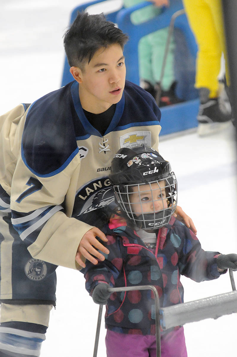 Langley Rivermen forward Kalen Szeto assisted two-year-old Rayna Tones from Pitt Meadows at the Sunday (Dec. 22) public skate at George Preston arena. (Dan Ferguson/Langley Advance Times)
