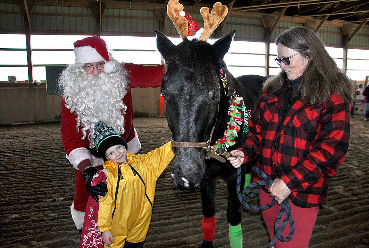 Santa and Aldergrove's Ethan Pritchard visited with Sprite, one of the VTEA therapy horses that was dressed up as a reindeer for the Dec. 15 open house. (Roxanne Hooper/Langley Advance Times)