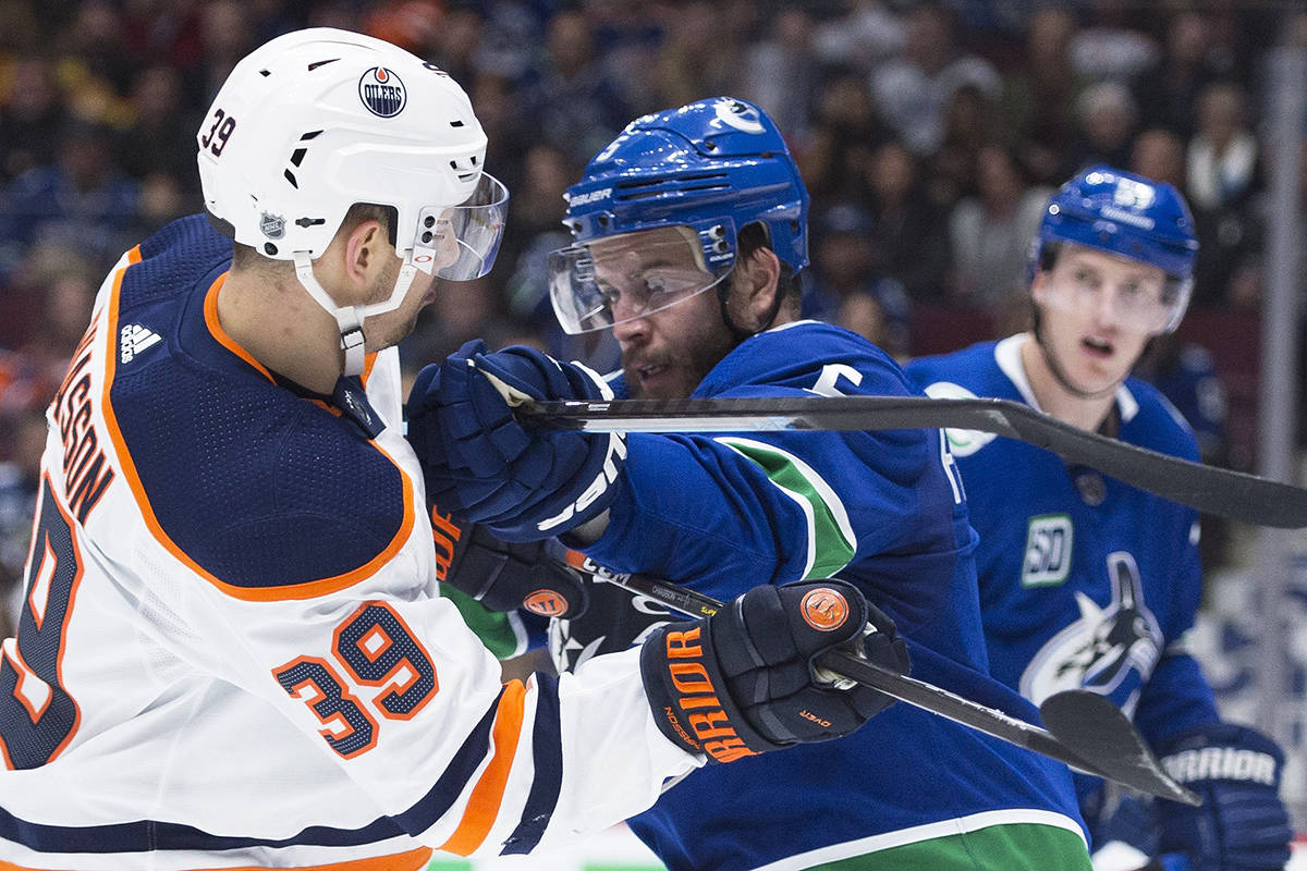 Vancouver Canucks defenceman Oscar Fantenberg (5) pushes Edmonton Oilers right wing Alex Chiasson (39) with his stick during first period NHL action in Vancouver on Monday, December, 23, 2019. THE CANADIAN PRESS/Jonathan Hayward