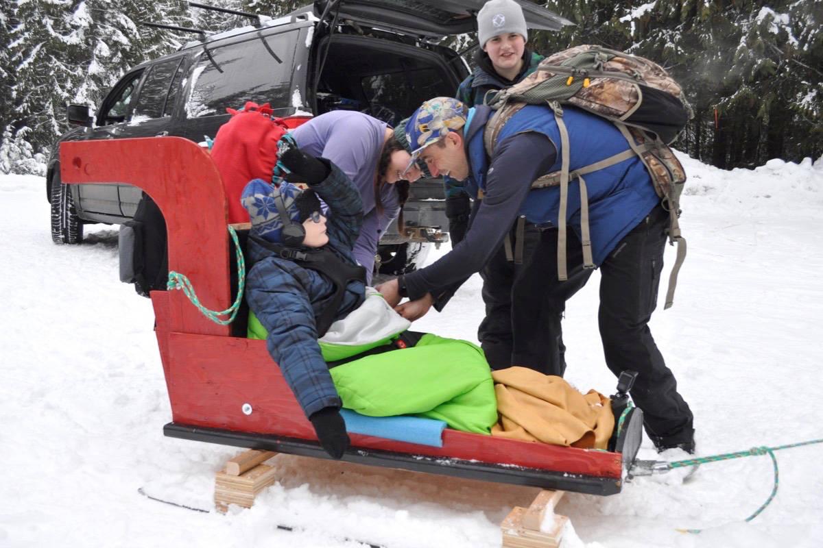 Teacher Chris Mieske helps Todd St. Pierre get settled in the sled. Photo: Tyler Harper
