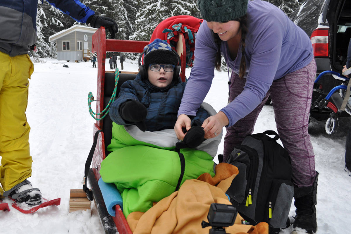 Trafalgar Middle School's Todd St. Pierre gets strapped into a special sled built for him by his fellow Grade 6 students for a winter hike. Photo: Tyler Harper