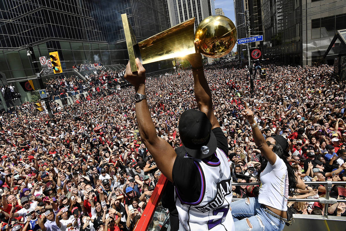 FILE - In this June 17, 2019, file photo, Toronto Raptors guard Kyle Lowry holds the Larry O'Brien Championship Trophy up for the fans during the NBA basketball championship team's victory parade. (Frank Gunn/The Canadian Press via AP, File)