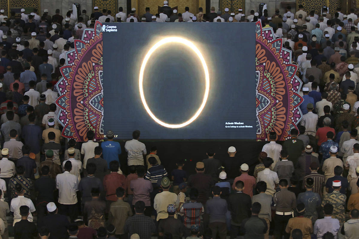 "Muslim men perform a special 'kusoof' prayer as a live report of the annular solar eclipse is broadcasted on a large screen at a mosque in Surabaya, East Java, Indonesia, Thursday, Dec. 26, 2019. People along a swath of southern Asia gazed at the sky in marvel on Thursday at a ""ring of fire"" solar eclipse. (AP Photo)"